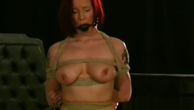 Naked honey stands with her big boobs tied up in ropes
