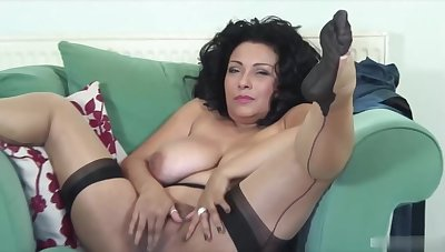 Hot mature brunette in erotic, black stockings is gently rubbing her shaved pussy with the addition of moaning